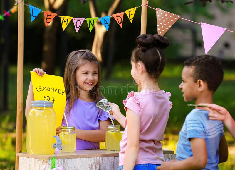 Little girl selling natural lemonade to kids. Summer refreshing drink royalty free stock photo