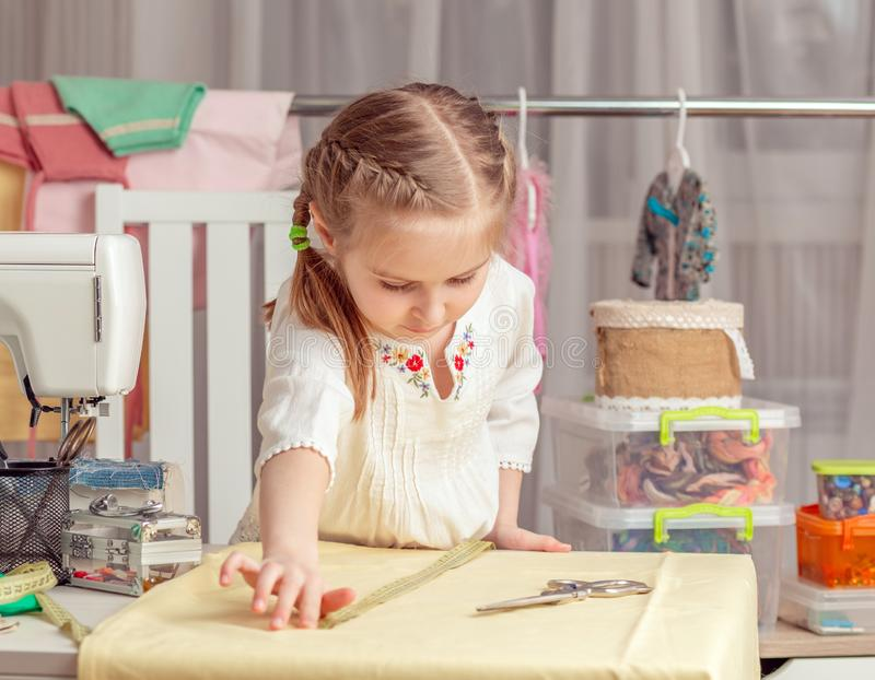 Little girl in a sewing workshop. Cute little girl in a sewing workshop measures the fabric stock photography