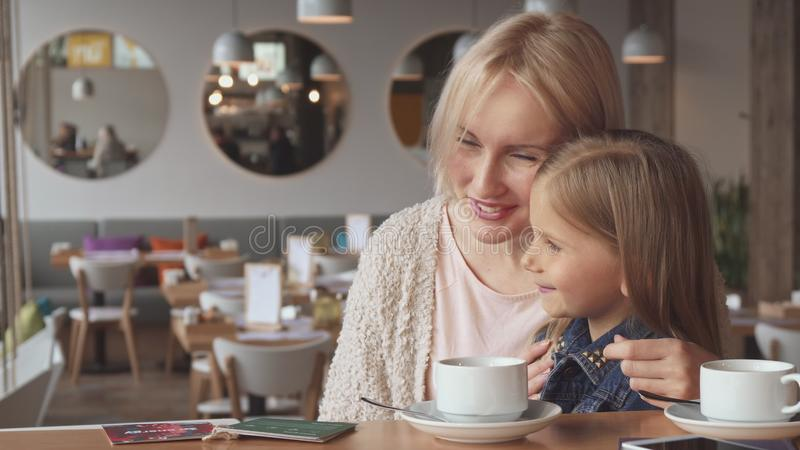 Little girl shares some secrets with her mother stock photo