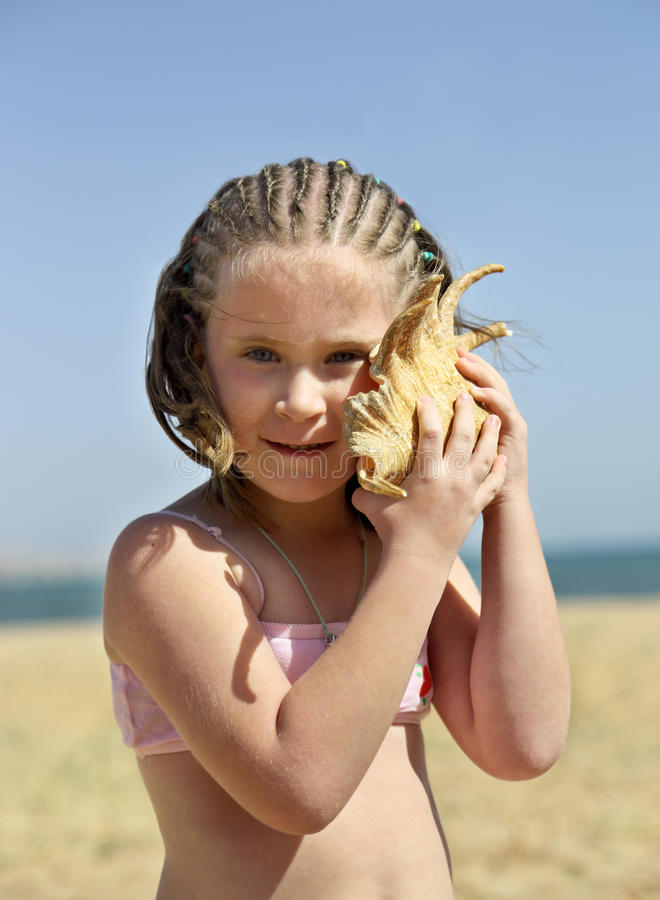 Little girl with shell on beach - vintage retro style royalty free stock images