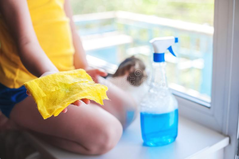 Little girl in shirt and blue shorts washes the windows at home. Daughter with a cat wash the window. Little girl in yellow shirt and blue shorts washes the stock photography