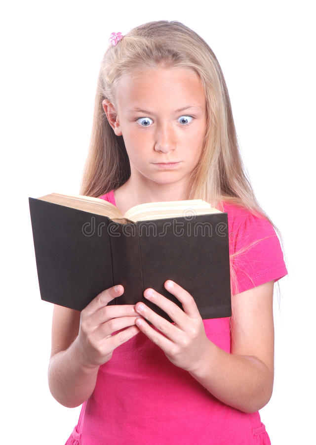 Little girl shocked about book. Portrait of a cute little Caucasian preteen girl child with shocked facial expression reading in a black book. Image isolated on stock photo