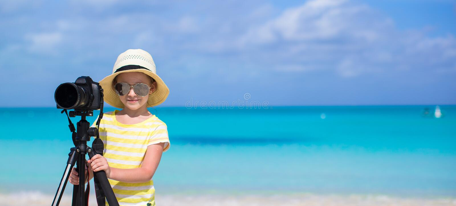 Little girl shooting with camera on tripod during royalty free stock photography