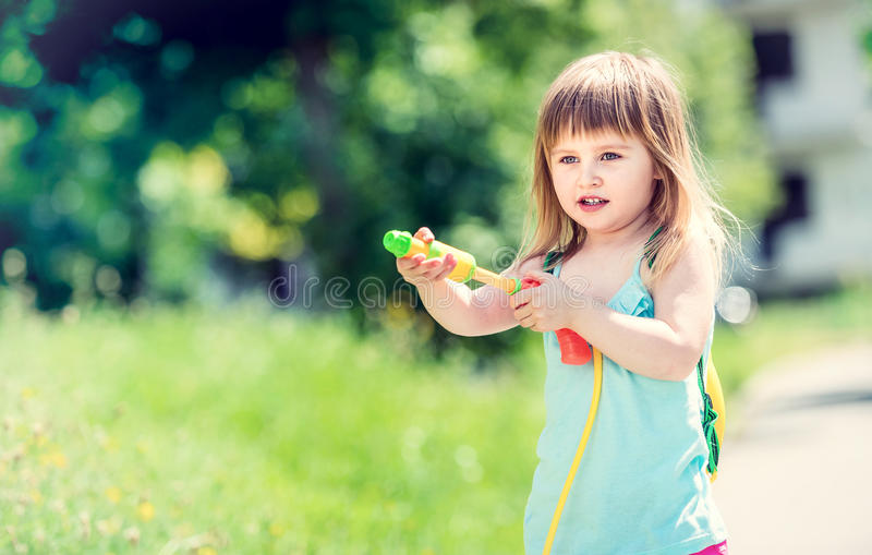 Little girl shooting with water pistol royalty free stock photos
