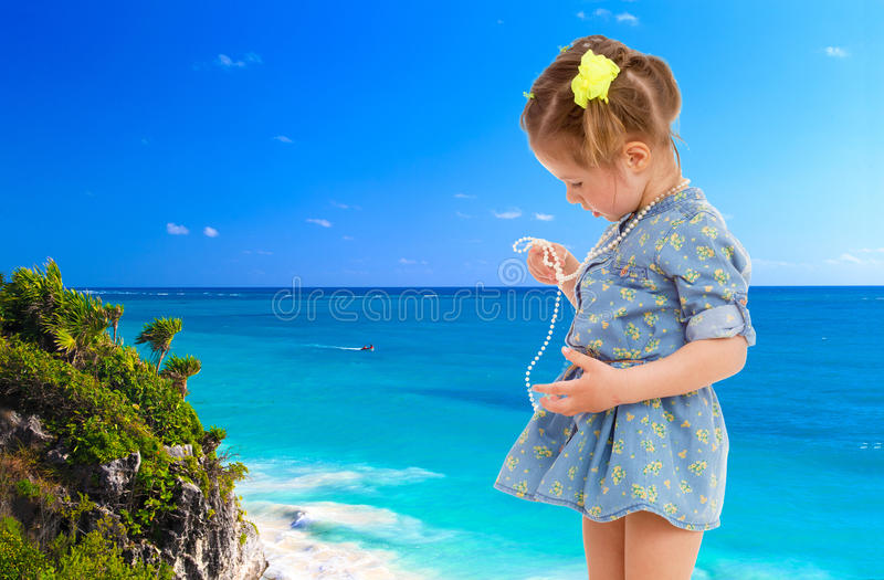 Little girl in a short blue dress on a sea background. stock photography