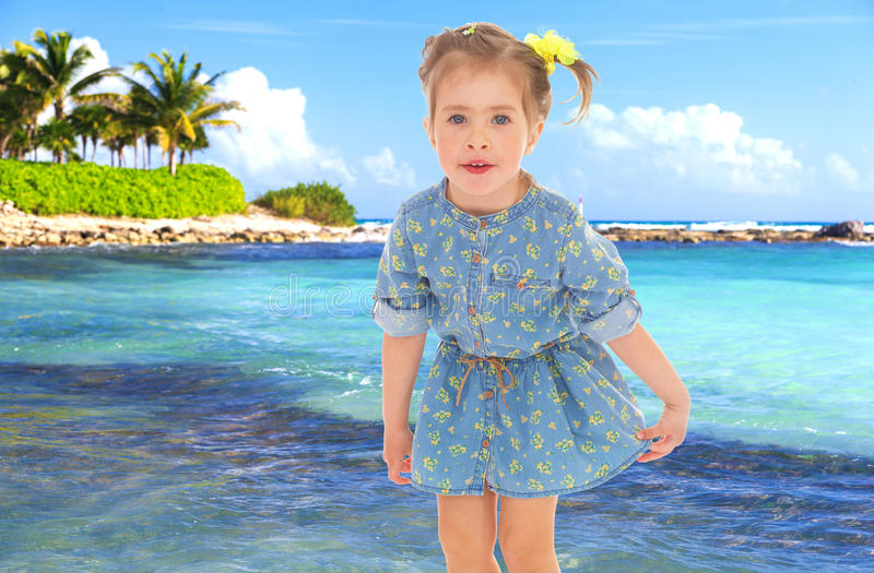 Little girl in a short blue dress on a sea background. royalty free stock images