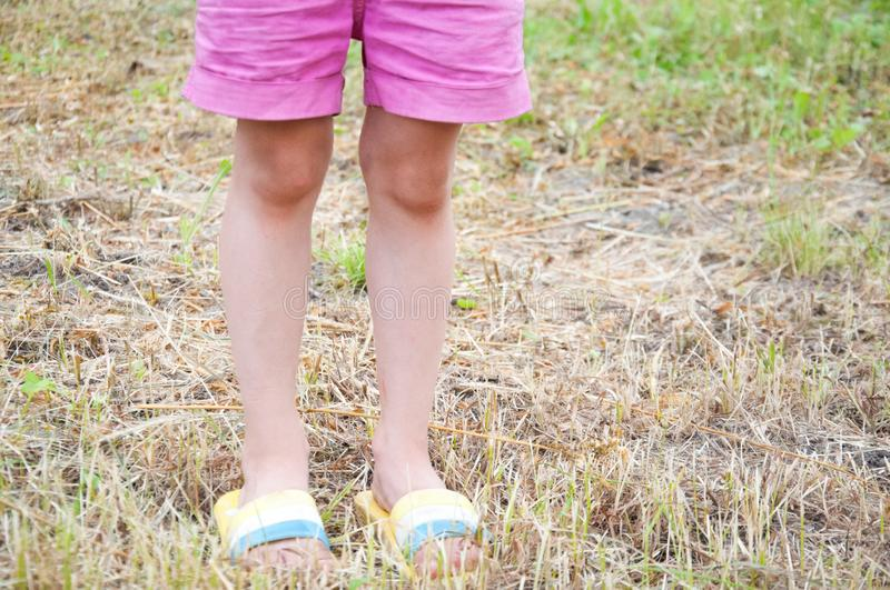 Little girl in shorts and flip-flops standing stock photography