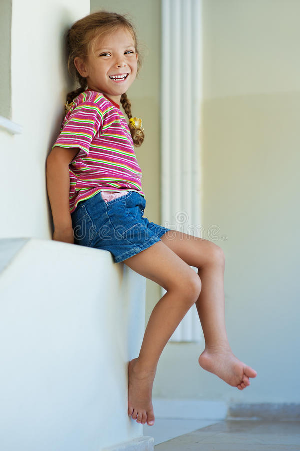 Little Girl In Shorts Sitting Royalty Free Stock Photography