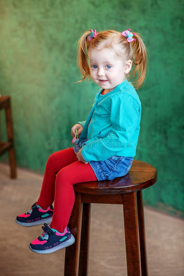 The little girl in shorts sitting on a chair. The concept of chi stock image