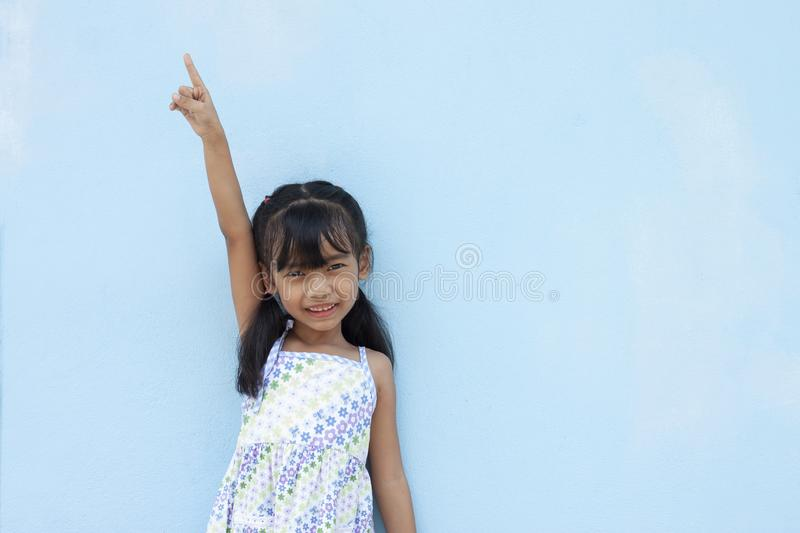Little girl show arm and index finger pointed up on blue wall background. Little girl show arm and index finger pointed up on blue cement wall background stock photos