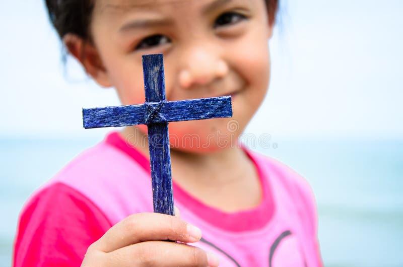 Little girl show the cross. stock photos