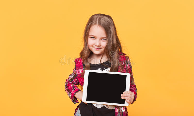 Little girl showing blank black tablet pc on yellow background stock photo
