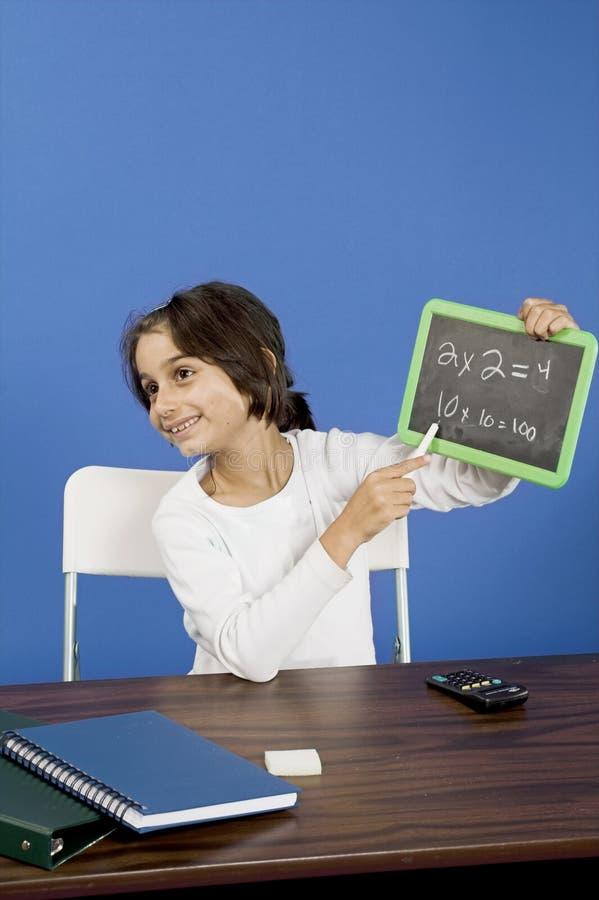 Little girl showing chalkboard stock photo