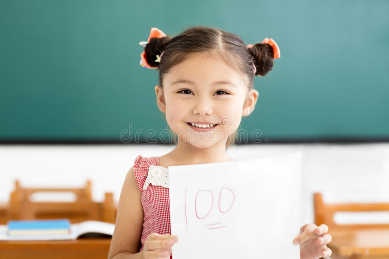 little girl showing exam paper with a plus in classroom stock photos