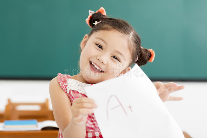 little girl showing exam paper with a plus in classroom stock image