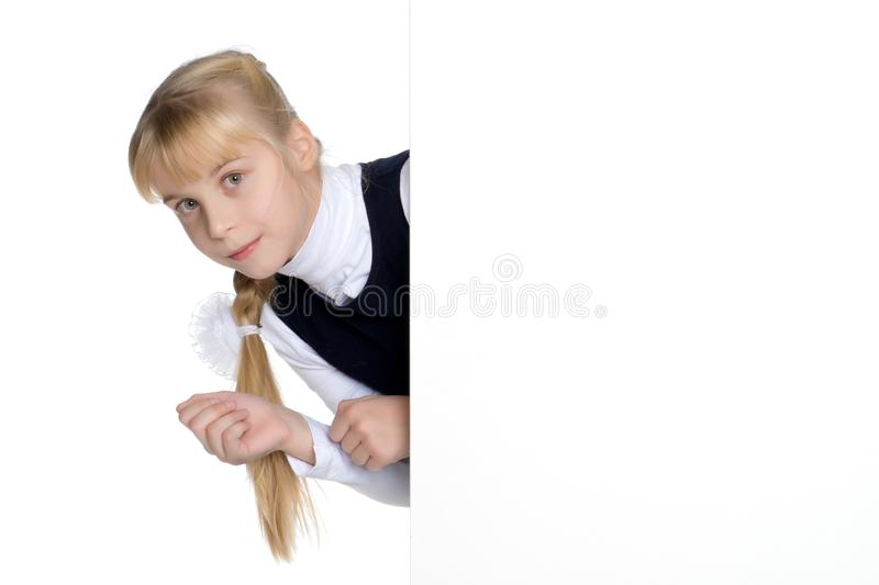Little girl is showing a finger on a white banner. stock photography