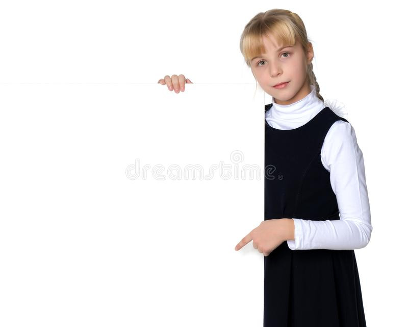 Little girl is showing a finger on a white banner. royalty free stock image