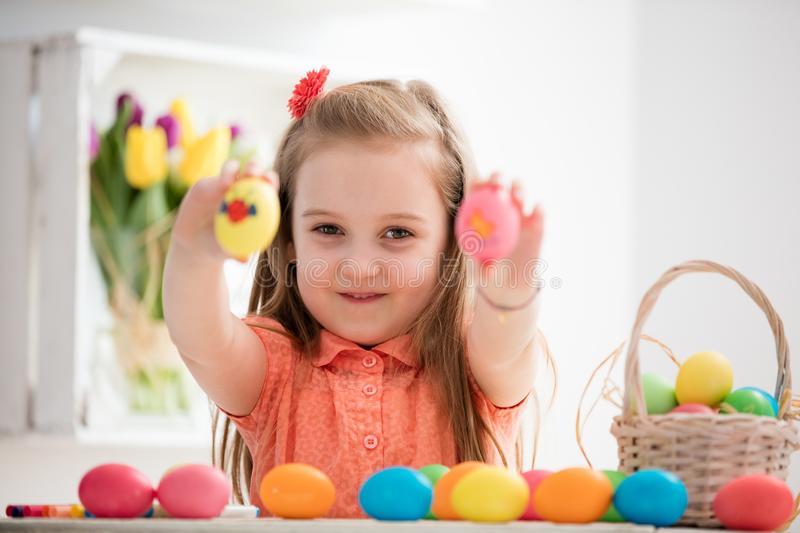 Little girl showing her hand-painted colorful eggs. stock photos