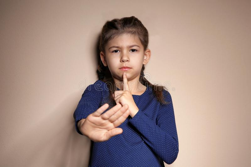 Little girl showing HUSH gesture in sign language on background royalty free stock photos