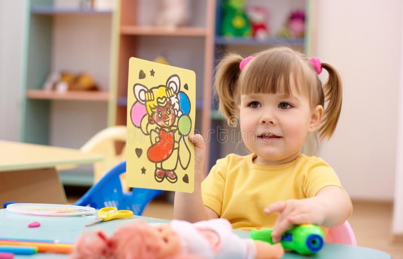 Little girl showing a picture in preschool royalty free stock photography