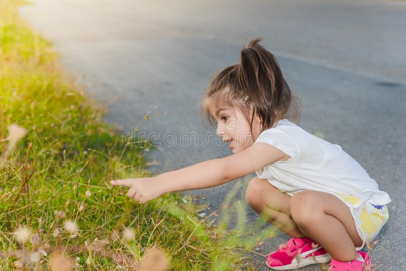 Little girl showing snails on a plant with her finger. Portrait of cute little girl showing snails on a plant with her finger in day time stock image