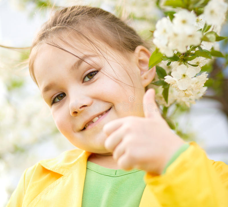Little girl is showing thumb up gesture. Near spring tree in bloom stock photography