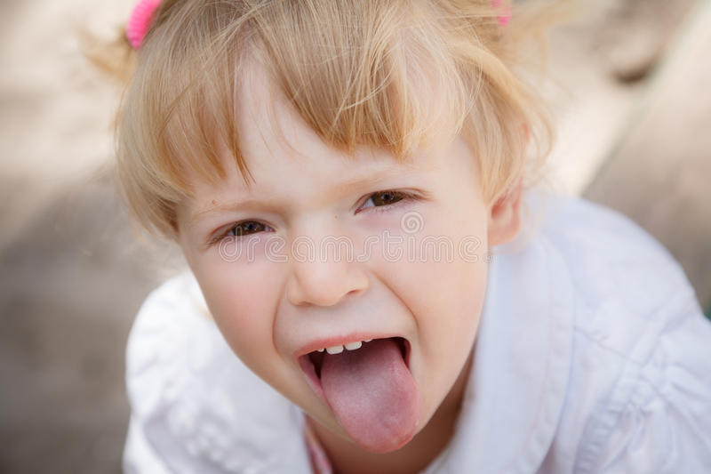 Little girl showing tongue royalty free stock image