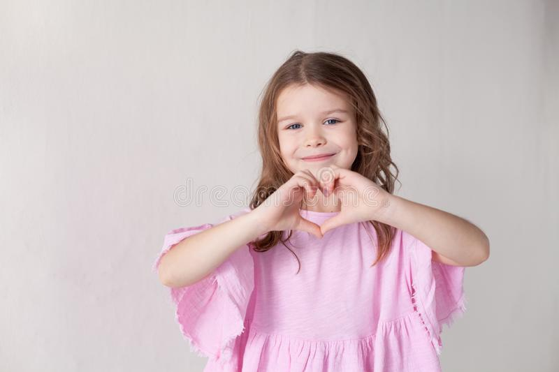 A little girl shows hands symbol heart stock photo