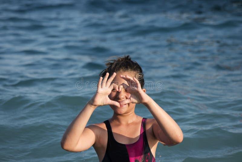 Little girl shows the heart stock photos