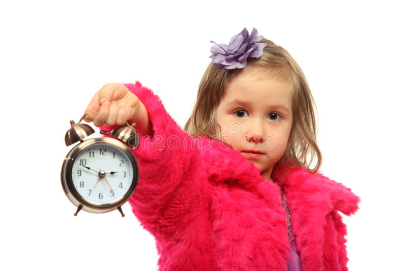 Little girl shows time on round alarm clock royalty free stock image
