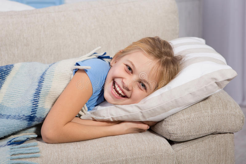 Little girl, sick lying on sofa and smiling. royalty free stock photo