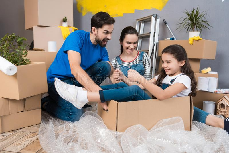 Little girl simulates flight on airplane, sitting in box next to parents. House renovation for sale. royalty free stock photography