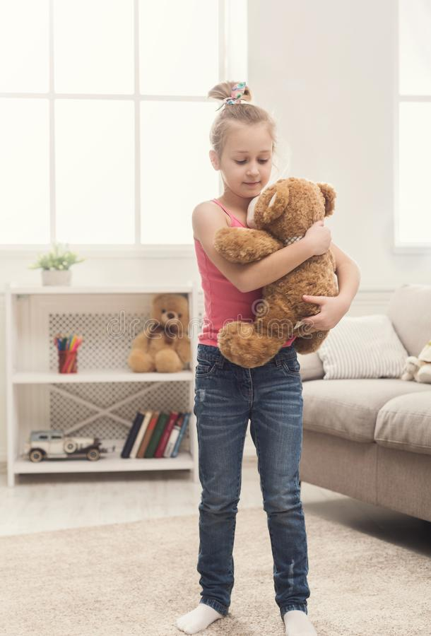 Little girl singing and dancing with bear at home royalty free stock photos