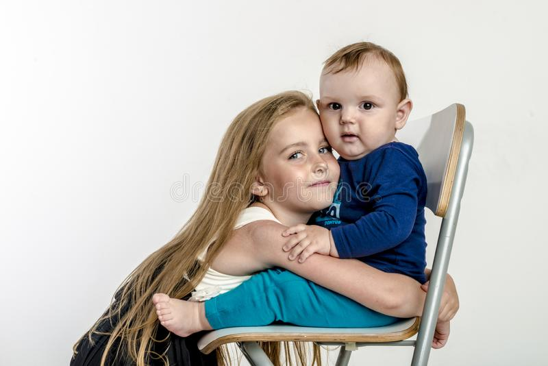 Little girl sister hugs the little boy`s brother sitting on the chair royalty free stock image