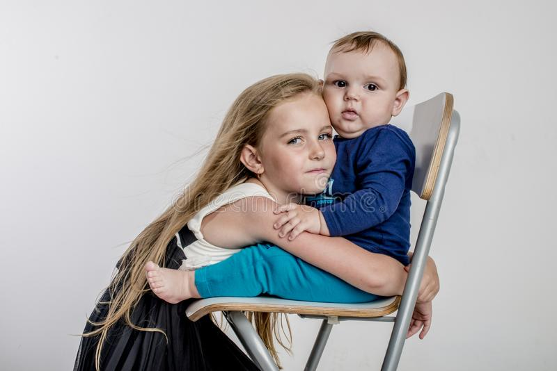 Little girl sister hugs the little boy`s brother sitting on the chair stock image
