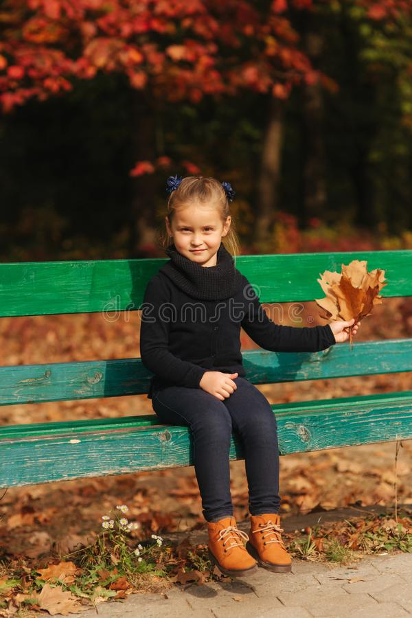 Little girl sit on the bench and look at the leaves. She collect leaves and take them with her. Autumn forest royalty free stock images