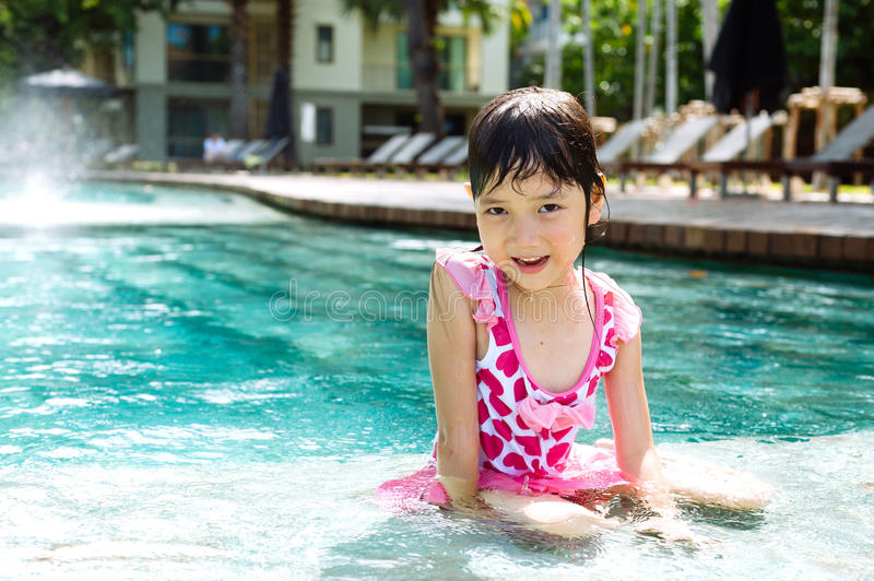Little girl sit at pool stock photography