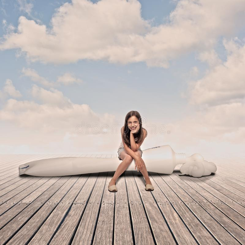 Little girl siting on a toothpaste tube royalty free stock photos