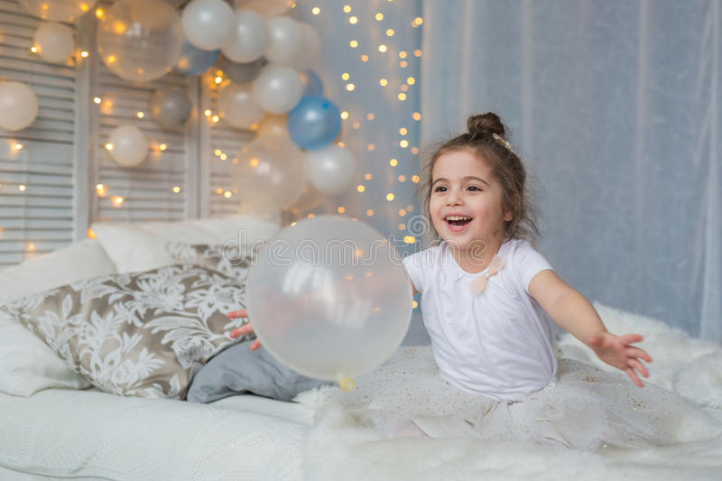 Little girl sits on a bed and plays with a balloon. Little girl sits on a bed and plays with balloon royalty free stock image