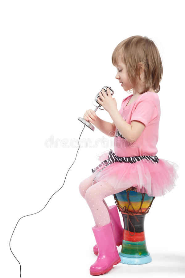 Little girl sits on djembe and sings royalty free stock photography