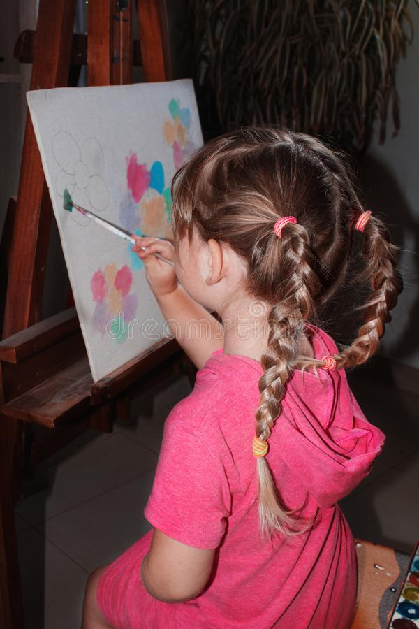 A little girl sits at the easel and draws. royalty free stock image