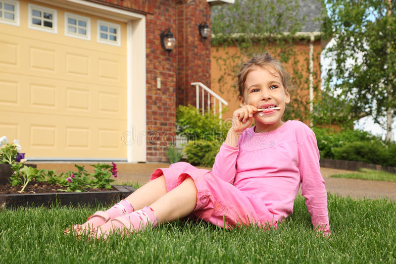 Download Little Girl Sits And Finishes Eating Ice Cream Stock Photo - Image: 27753944