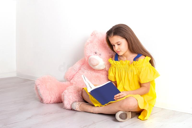 Studio shot of a  little  girl wearing yellow sundress  sits on the floor against the wall with a big pink teddy bear and reads a. A little  girl  sits on the royalty free stock photos