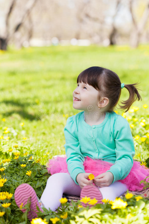 Little girl sits on a glade among flowers royalty free stock images