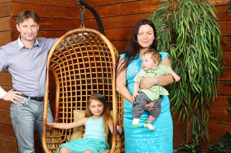 Little girl sits in hanging chair and father, mother with baby stock photo
