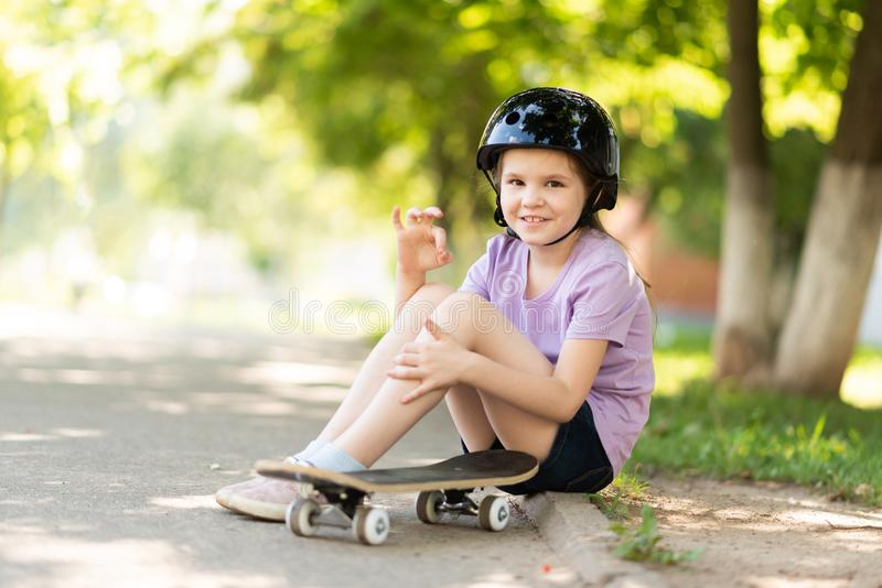 A little girl sits in a helmet and with a skateboard, and shows the sign okay. For any purpose royalty free stock image