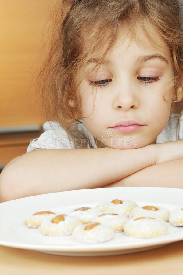 Little girl sits and sadly looks at plate with cookies stock photography