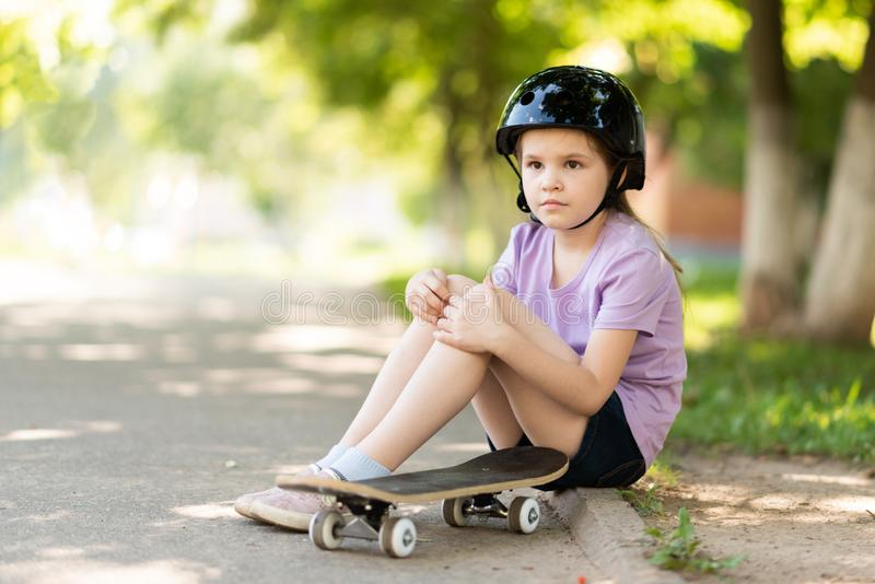 A little girl sits on a skateboard, wearing a helmet, and looks into the distance. For any purpose stock images