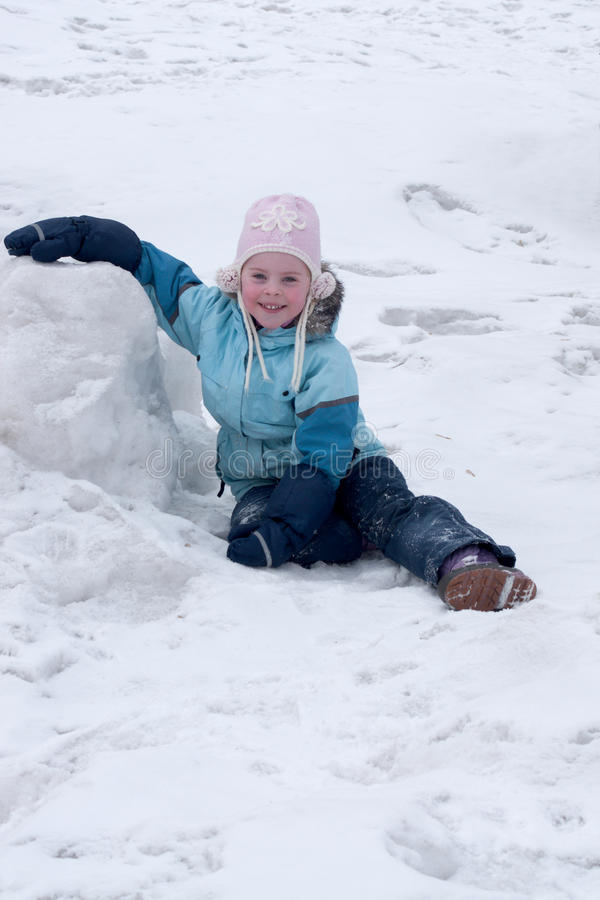 Little girl sits on snow stock images