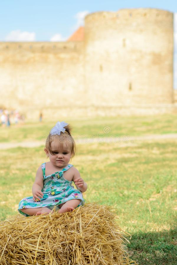 A little girl sits on a straw in a dress and a bow near the wall of the fortress royalty free stock photo